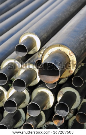 Rusty steel pipe with heat insulation on construction site, DOF - stock photo