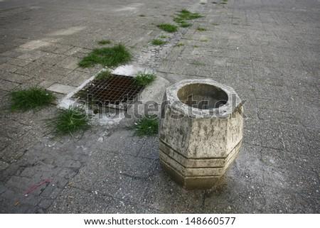 rusty stone trash can in street near manhole - stock photo