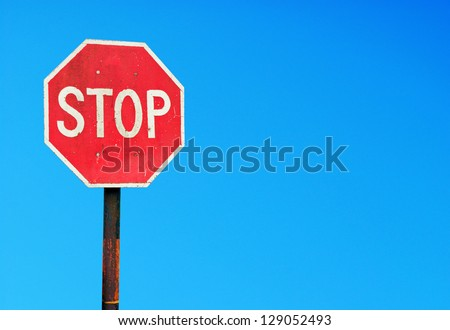 rusty stop sign on a metal pole against a vibrant blue sky (copy-space for your design) - stock photo