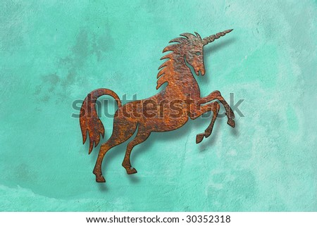 rusty unicorn on green wall - stock photo
