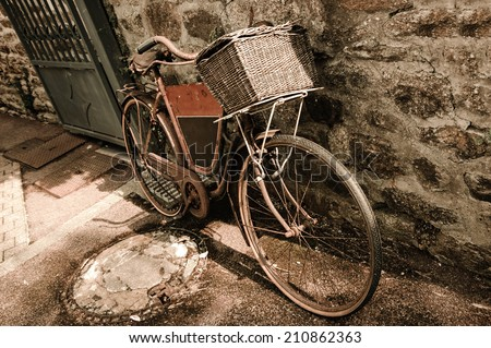 Rusty vintage bicycle with black board for entering a text (advertisement, menu etc) and wicker basket leaning on a stone wall. Brittany, France. Aged photo. - stock photo