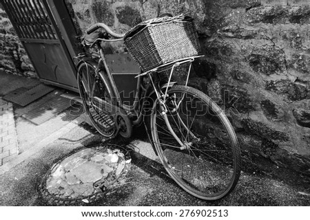 Rusty vintage bicycle with black board for entering a text (advertisement, menu etc) and wicker basket leaning on a stone wall. Brittany, France. Aged photo. Black and white. - stock photo