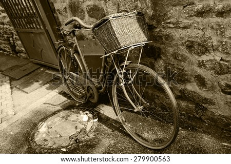 Rusty vintage bicycle with black board for entering a text (advertisement, menu etc) and wicker basket leaning on a stone wall. Brittany, France. Aged photo. Sepia. - stock photo