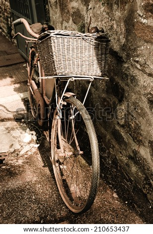 Rusty vintage bicycle with wicker basket leaning on a stone wall. Brittany, France. A game of light and shadow. Aged photo. - stock photo