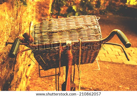 Rusty vintage bicycle with wicker basket leaning on a stone wall. Brittany, France. Closeup. Back view. Aged photo. - stock photo