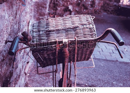 Rusty vintage bicycle with wicker basket leaning on a stone wall. Closeup. Back view. Toned photo. - stock photo