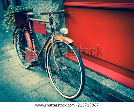 Rusty vintage red bicycle leaning with on red wooden board (useful for entering a text advertisement, menu etc) and carrying plants in wooden box as decoration. Retro aged photo. - stock photo