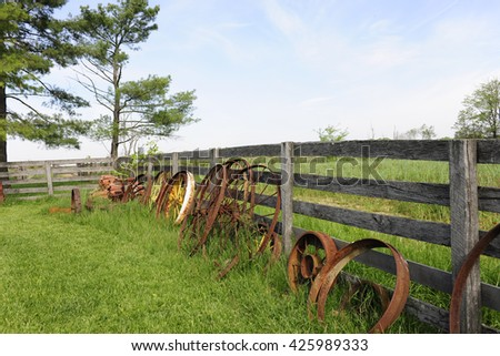 Rusty wagon wheels leaning against a rustic rail fence that's surrounded by grassy fields. - stock photo