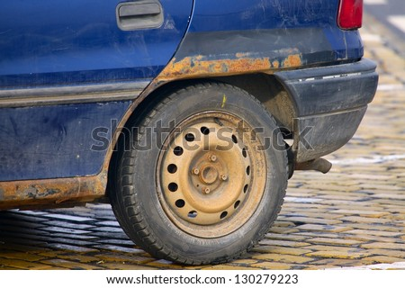 Rusty wheel of a very old car - stock photo