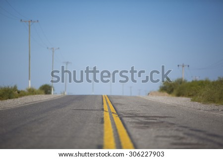 Ruta 40, famous highway with yellow line against a blue sky, long road stretching out into the distance in North of Argentina - stock photo