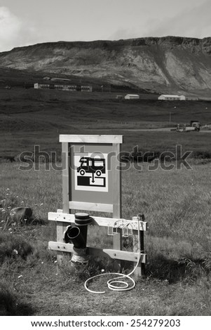 RV camping sewage dump station at a campground in Iceland. Focus on the sign. Black and white monochrome tone. - stock photo