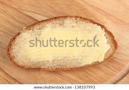 rye bread and butter on wooden board - stock photo