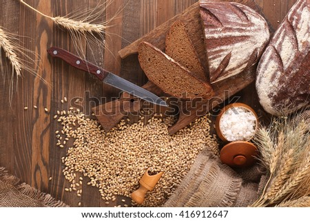 rye bread on a cutting board, salt rye ears against the backdrop of wooden planks - stock photo