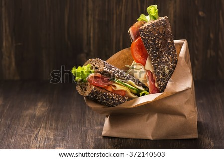 Rye bread sandwiches with ham, cheese and vegetables in a craft  - stock photo
