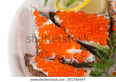 Rye bread with butter and red caviar with lemon and dill as a sandwich. Macro. Photo can be used as a whole background. - stock photo