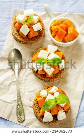rye bruschetta with honey pumpkin and goat cheese on a blue background. tinting. selective focus on mint on the bottom bruschetta - stock photo