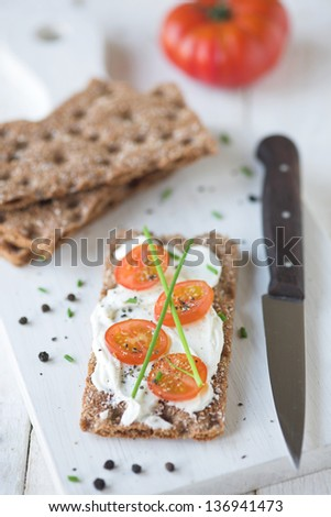 Rye cracker with cream cheese & sliced tomato served on a chopping  board - shallow dof - stock photo