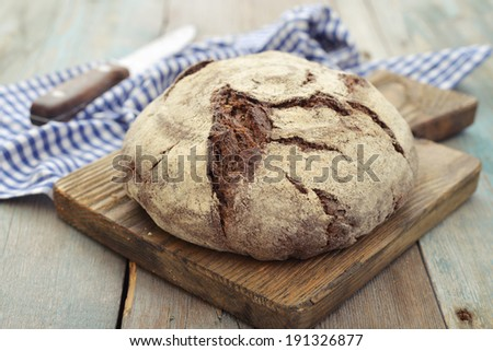 Rye round bread  on cutting board with knife on wooden background - stock photo