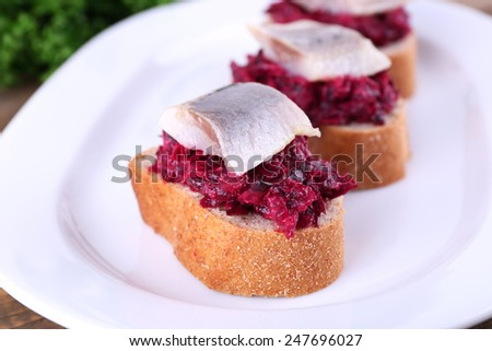 Rye toasts with herring and beets on plate close up - stock photo