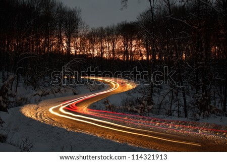 S curve on a forest road at night, just after sunset. The lights are created by the passing cars. - stock photo