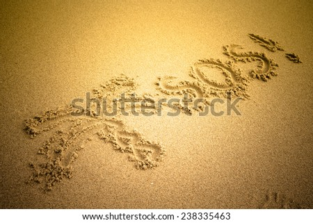 S.O.S written in the sand.Beach background. Top view. tinted  - stock photo