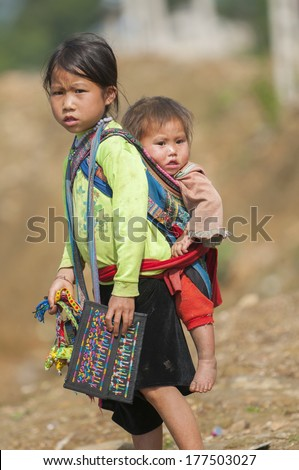 SA PA, VIETNAM - MAY 28, 2011: Unidentified kids of Black Hmong ethnic minority tribe carries her brother in Sa Pa, Northern Vietnam. - stock photo