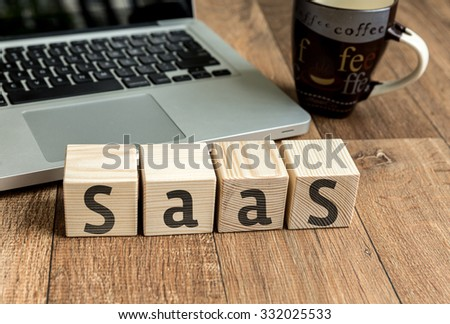 SAAS written on a wooden cube in front of a laptop - stock photo