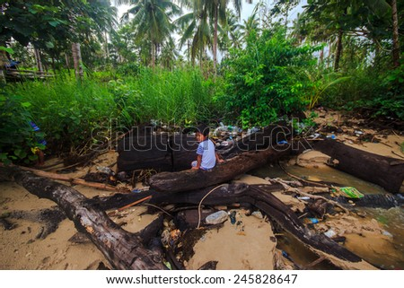 SABAH, MALAYSIA - DISEMBER 21 : An unidentified child playing with rubbish on December 21, 2014 in Kudat, Sabah, Malaysia.  Children here do not attend school due to lack of resources. - stock photo