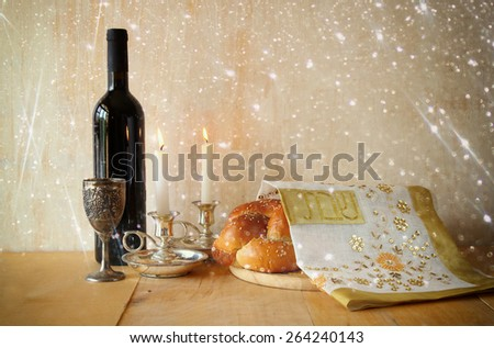 Sabbath image. challah bread and candelas on wooden table. glitter overlay  - stock photo