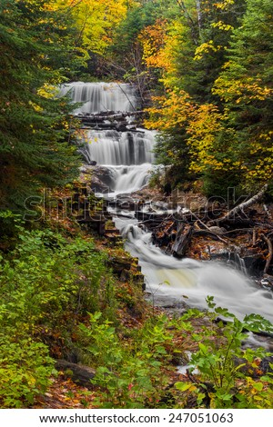 Sable Falls, a waterfall in Upper Peninsula Michigan's Pictured Rocks National Lakeshore, is surrounded by fall color and evergreen trees. - stock photo