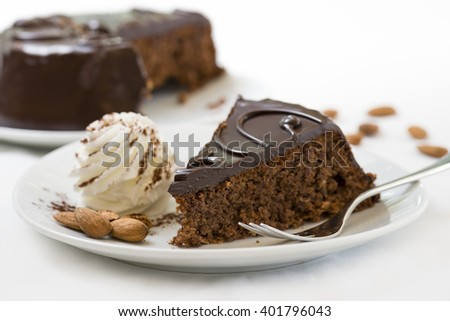 sacher cake slice on plate with fresh cream and almonds - stock photo