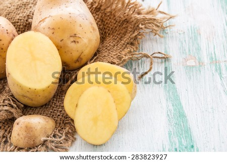 Sack fresh organic potatoes on a wooden table background - stock photo