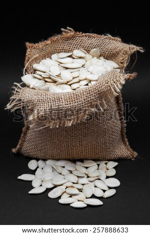 sack of seeds of pumpkin on black background - stock photo