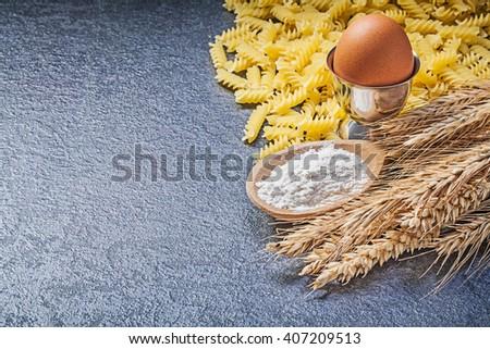 Sack spiral macaroni wheat rye ears wooden spoon flour eggcup boiled egg on black background. - stock photo
