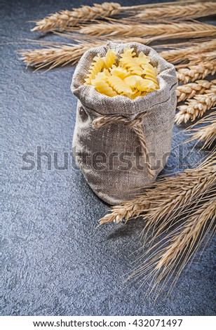 Sack with spiral macaroni golden wheat rye ears on black background. - stock photo