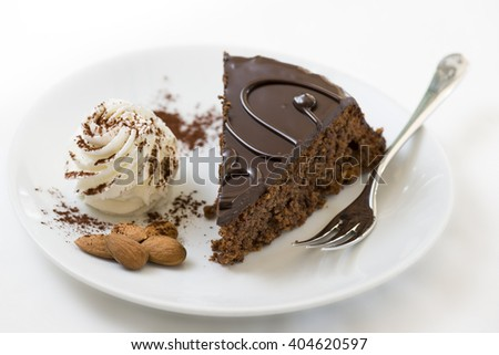 sacker cake slice on plate with fresh cream and almonds - stock photo