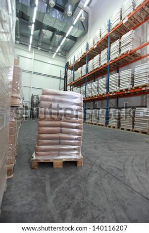 Sacks on wooden pallet inside storehouse - stock photo