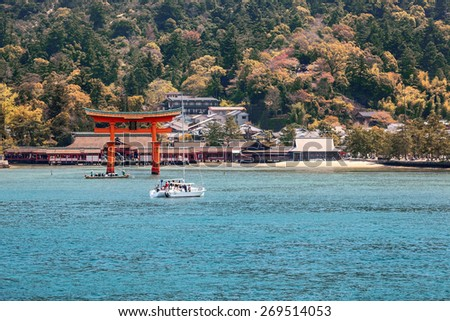 Sacred red Torii and Itsukushima Shinto shrine on the shore of the island of Miyajima, Japan. View from the Hiroshima gulf - stock photo