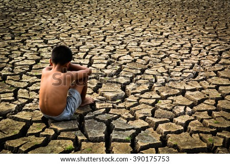 Sad a boy sitting on dry ground .drought - stock photo