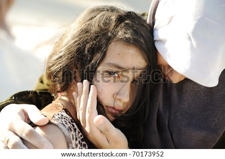 sad abused girl in arms of her mom, gaza - egypt - stock photo
