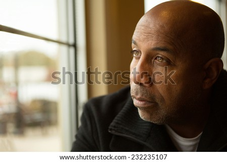 Sad African American man looking out the window. - stock photo