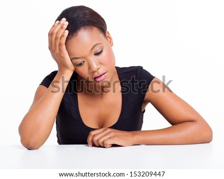sad african american woman sitting at a desk on white background - stock photo