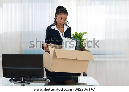 Sad African Businesswoman Carrying Box With Her Belongings In Office - stock photo