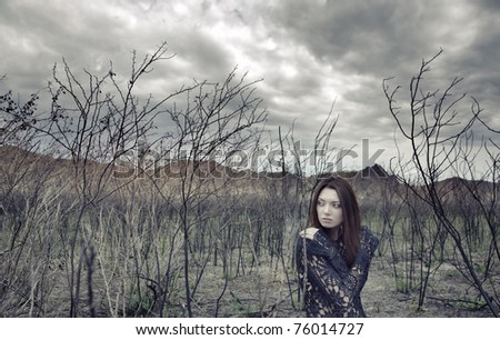 Sad alone woman in the dead bushes and thunderous sky on a background. Artistic colors added for movie effect - stock photo