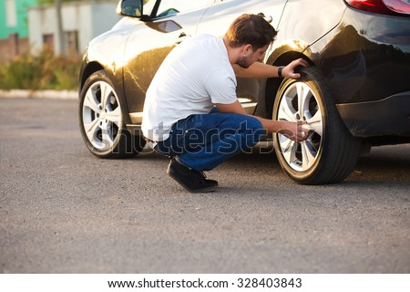 Sad and depressed man sitting near car with punctured tire - stock photo