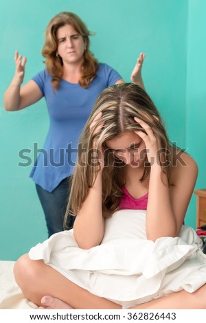 Sad and depressed teenage girl with her mother yelling at her - stock photo