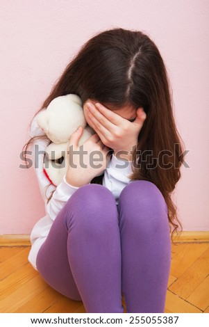 Sad and Lonely Girl Crying with a Hand Covering her Face. Concept: Domestic and Family Violence. - stock photo