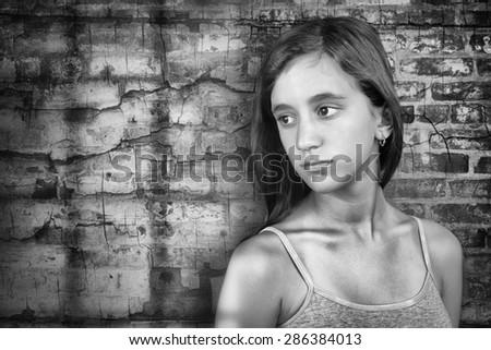 Sad and lonely teenage girl standing next to a grunge brick wall - stock photo