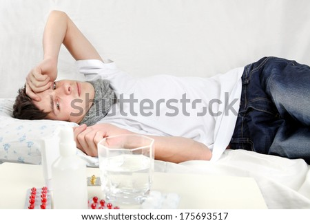 Sad and Sick Young Man lying on the Bed with Pills on foreground - stock photo