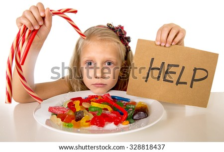 sad and vulnerable Caucasian female child asking for help  eating dish full of candy and gummies holding sugar spoon in sweet abuse dangerous diet and unhealthy nutrition concept isolated on white - stock photo